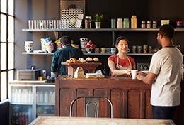woman serving man coffee in coffee shop